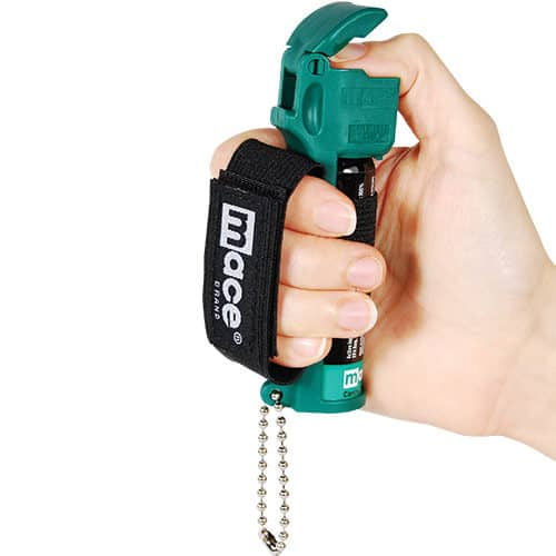 Mace® Canine Repellent Viewed in Hand Demonstrating Wrist Strap with Thumb On Trigger